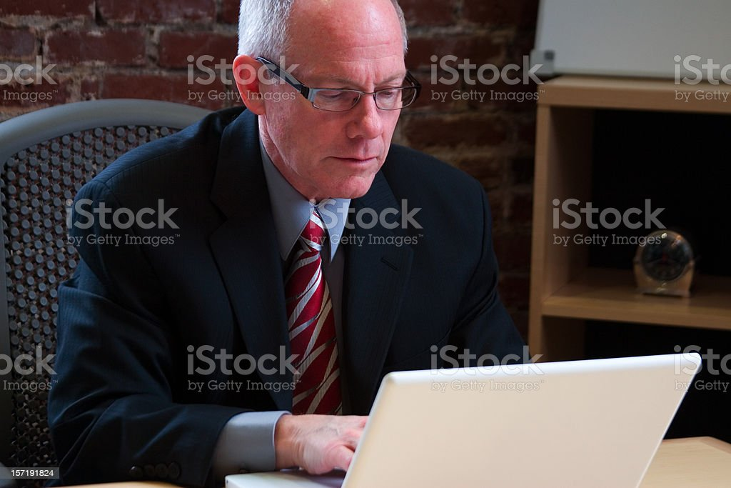 Active Senior Citizen Businessman Using Laptop in Office royalty-free stock photo