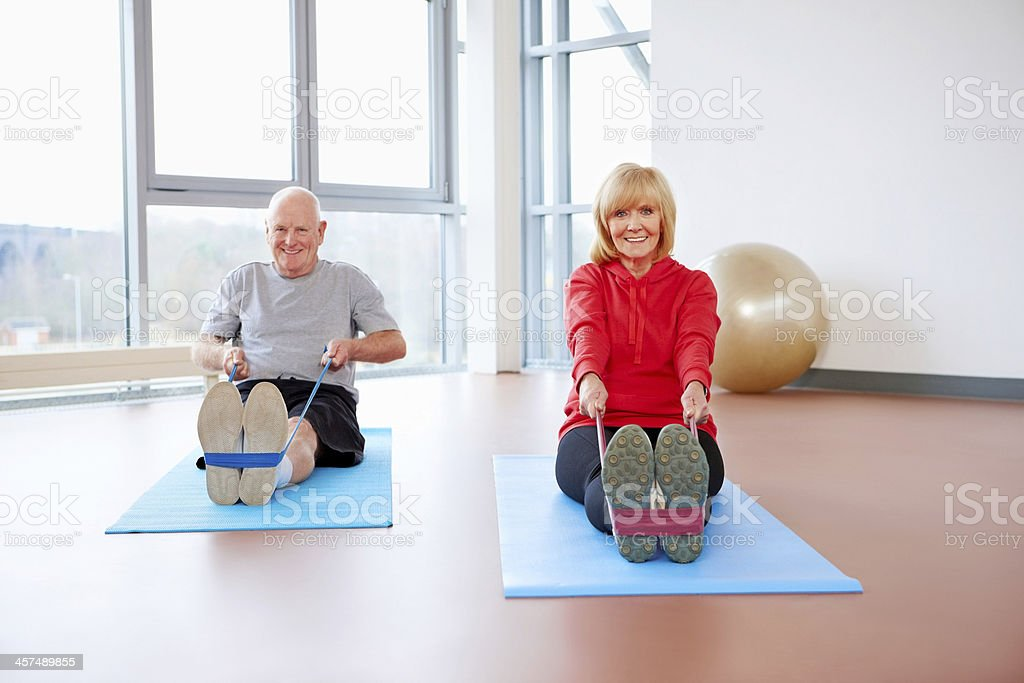 Active senior couple doing exercises with a resistance band stock photo
