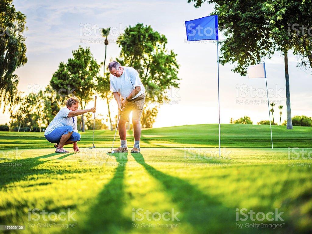 Active senior couple playing golf royalty-free stock photo