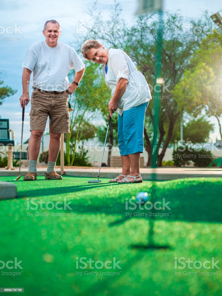 Active senior couple playing golf stock photo