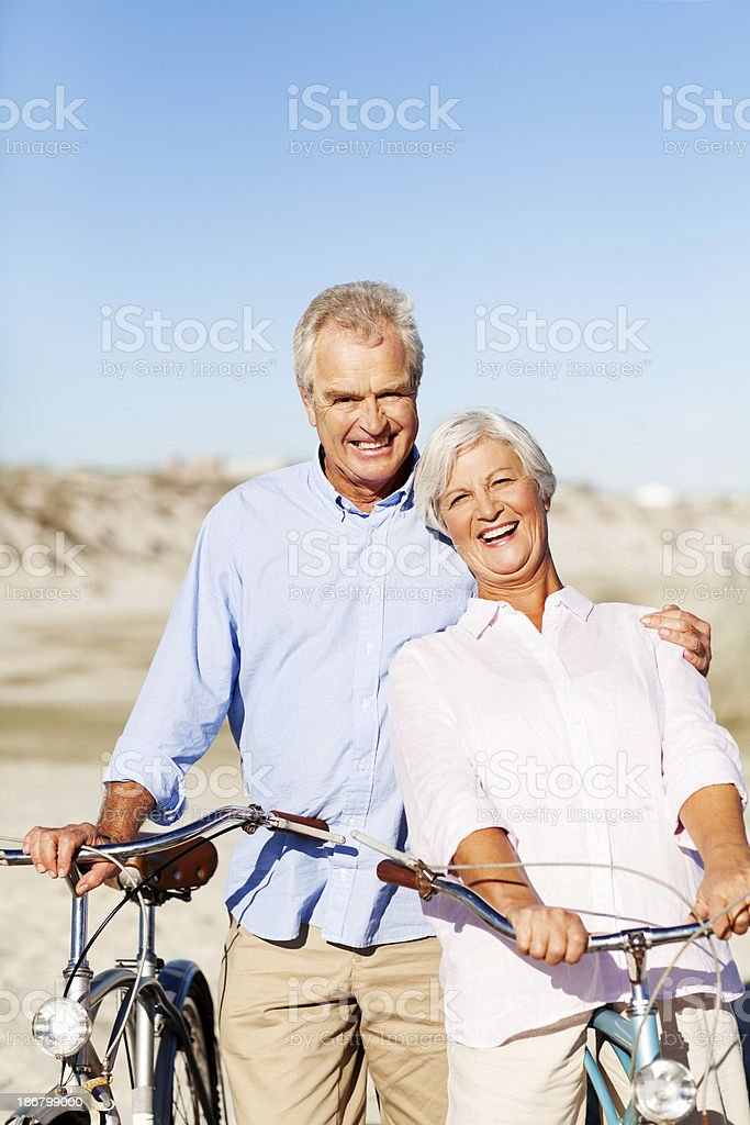 Active Senior Couple With Bicycles Standing On Beach royalty-free stock photo