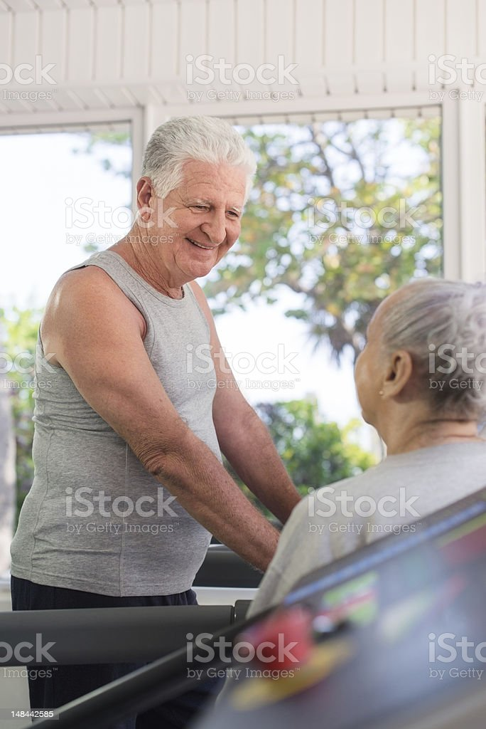 Active senior friends talking and working out in fitness club royalty-free stock photo