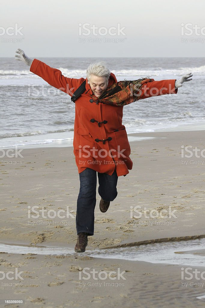 Active senior jumping on the beach stock photo