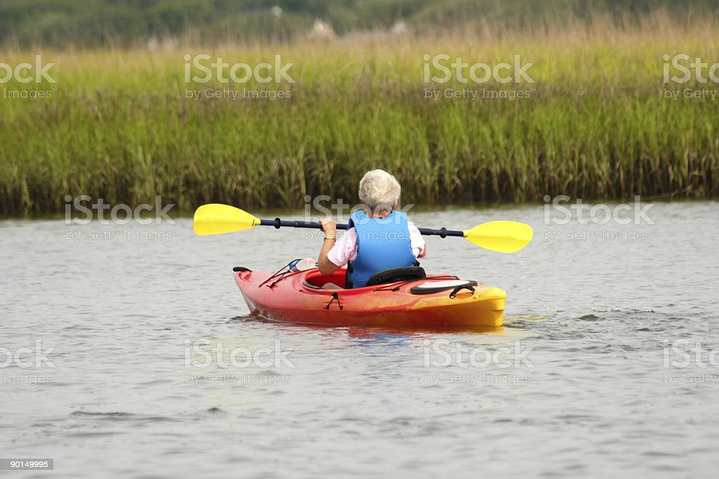 Active senior lady kayaking on the intracoastal royalty-free stock photo