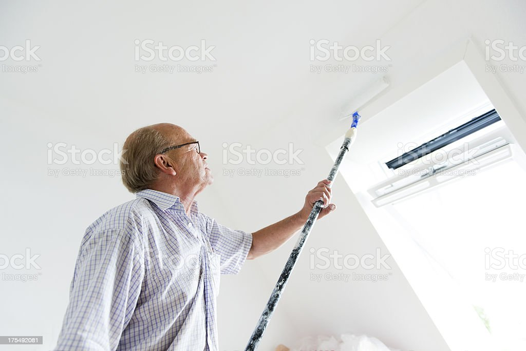 Active senior man is painting a wall in his home. royalty-free stock photo