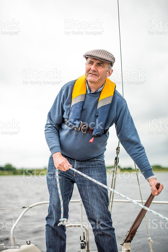 Active senior man sailing in the open waters stock photo