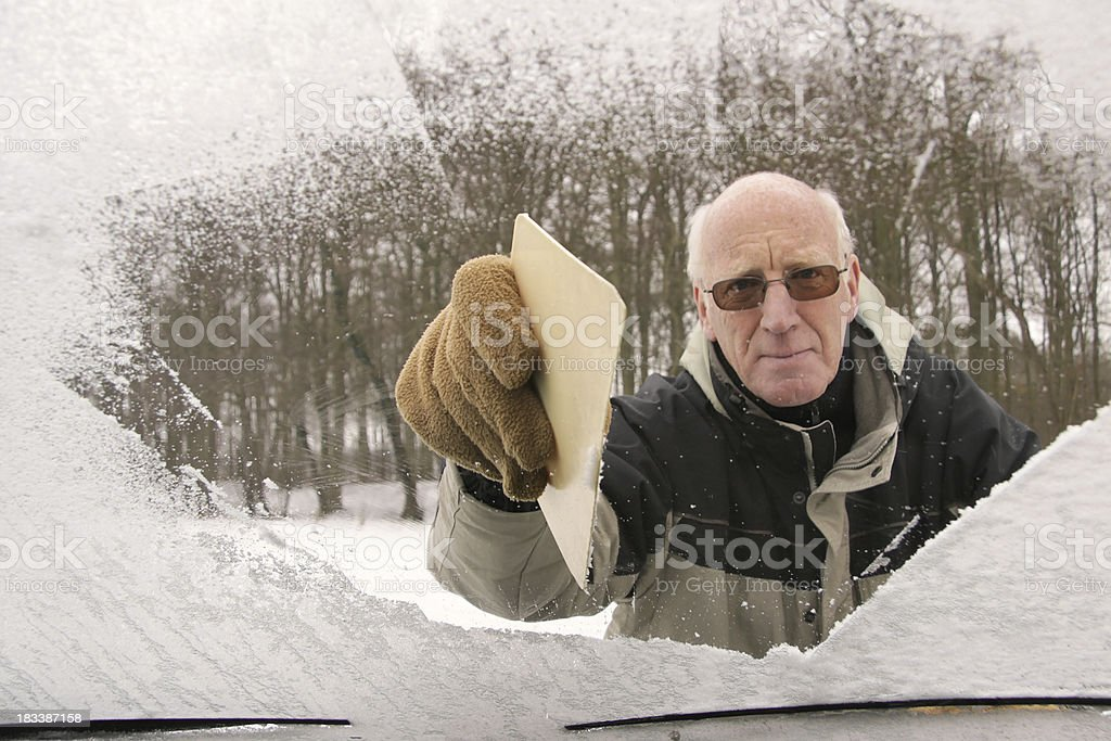 Active senior man scraping car windshield stock photo