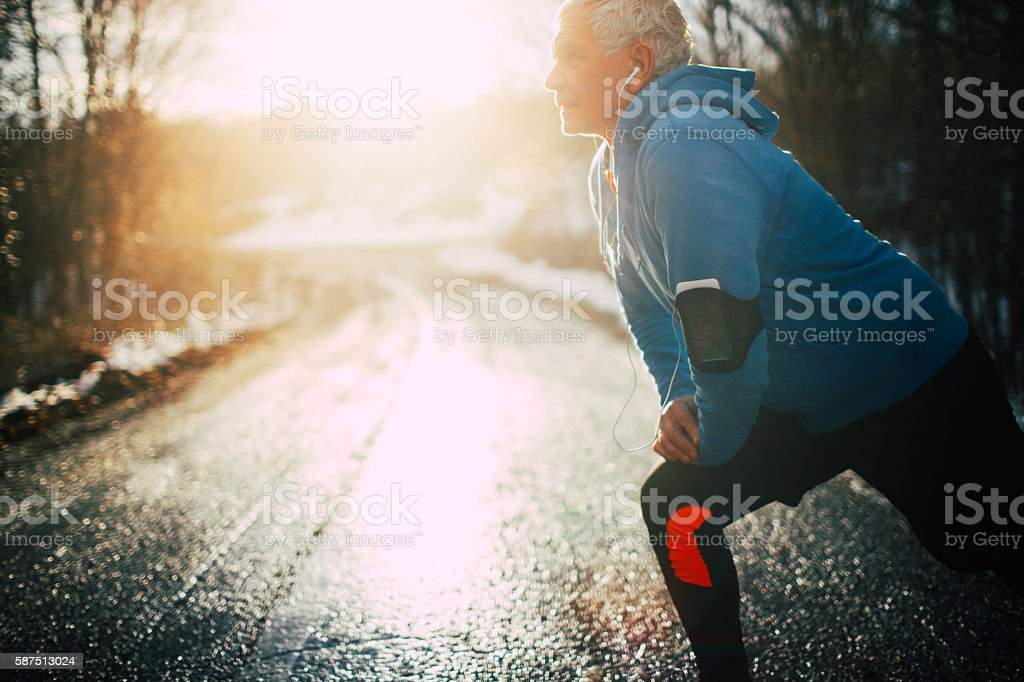 Active senior man stretching stock photo