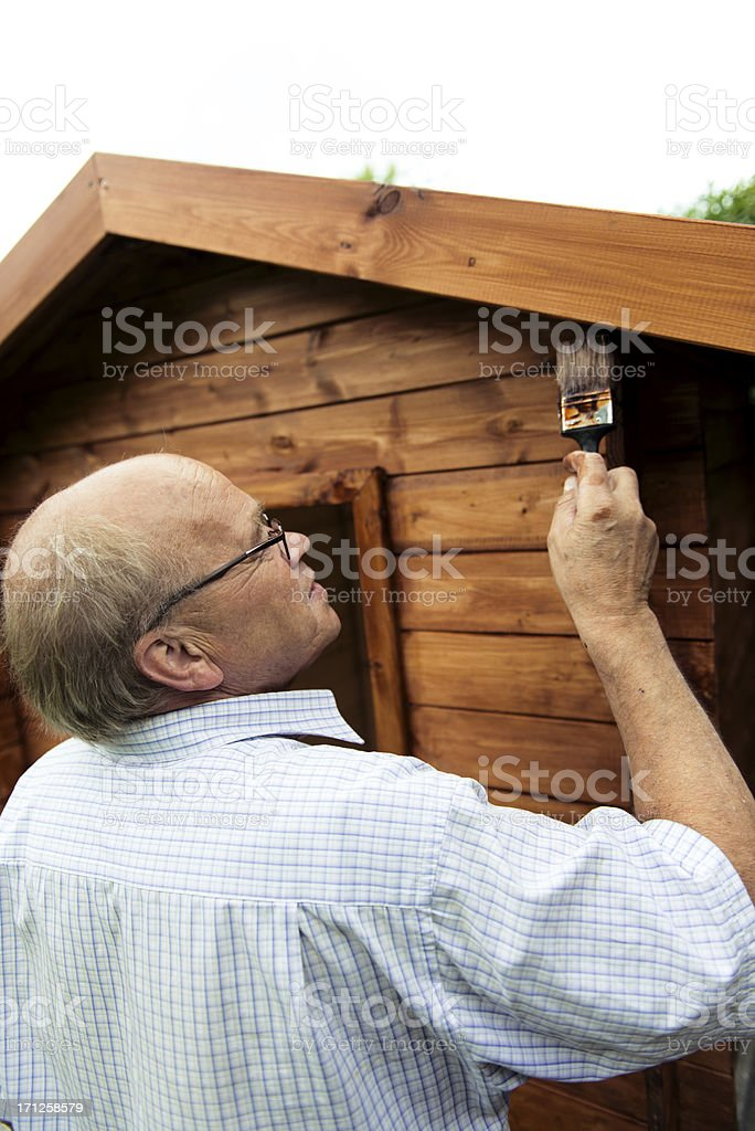 Active senior paints a house made of wood royalty-free stock photo