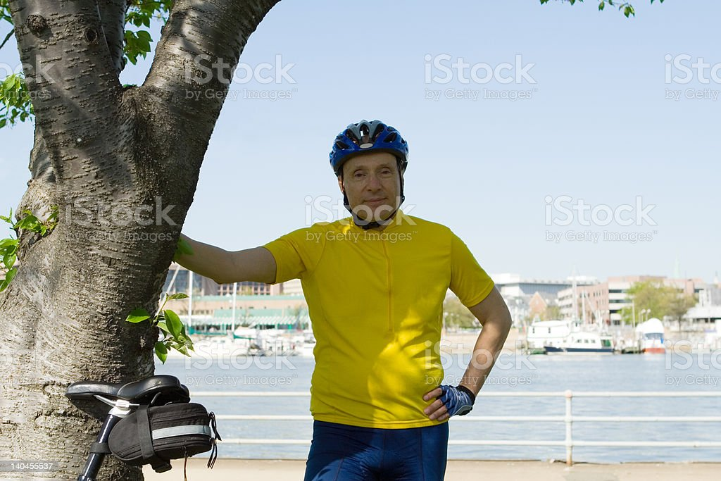 Active Senior Standing Next to His Bike by a River royalty-free stock photo