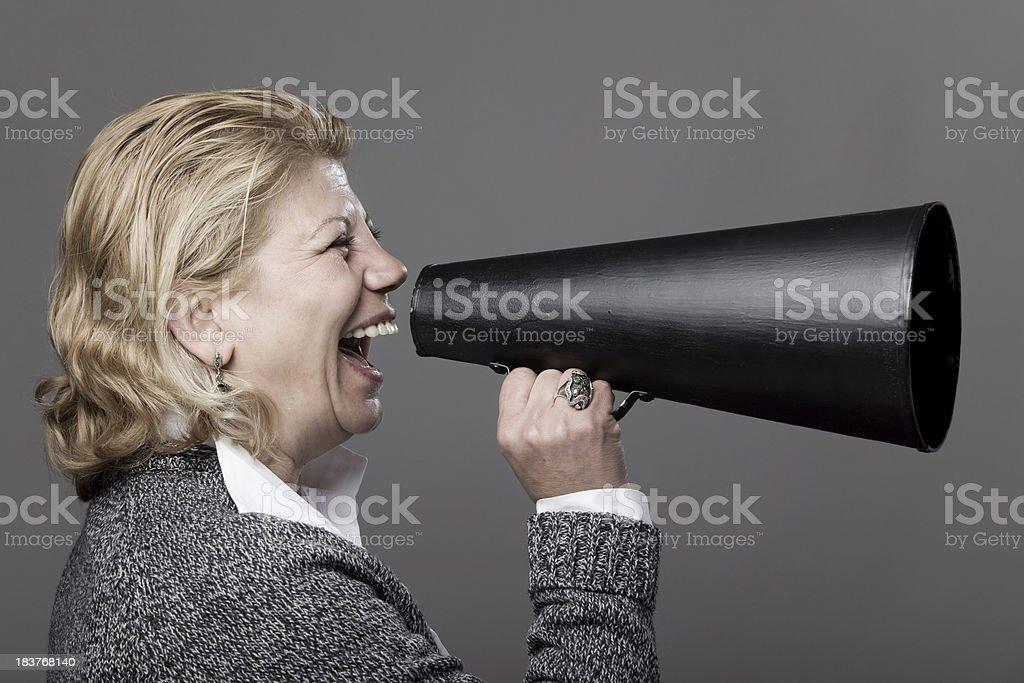 Active senior woman communicating via old fashioned megaphone royalty-free stock photo