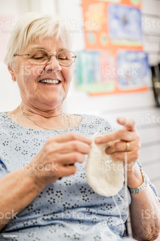 Active Senior Woman Crocheting At The Community Center stock photo