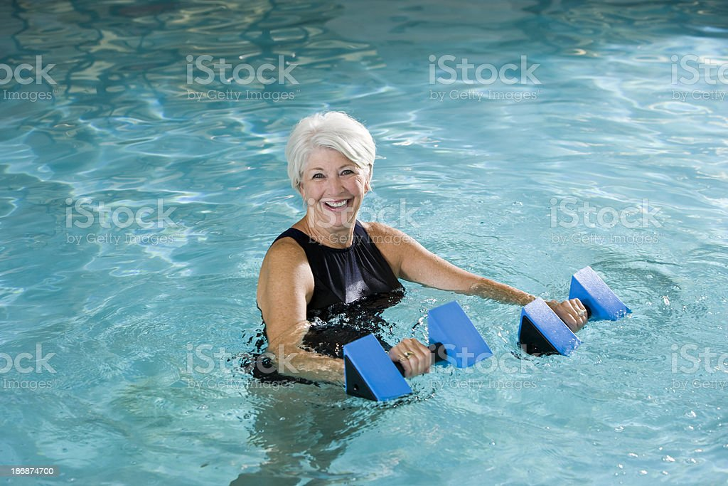 Active senior woman doing water aerobics royalty-free stock photo