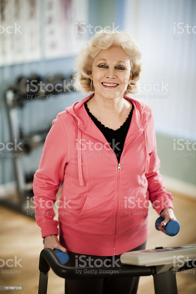Active Senior Woman Exercising with Dumbells on Treadmill stock photo
