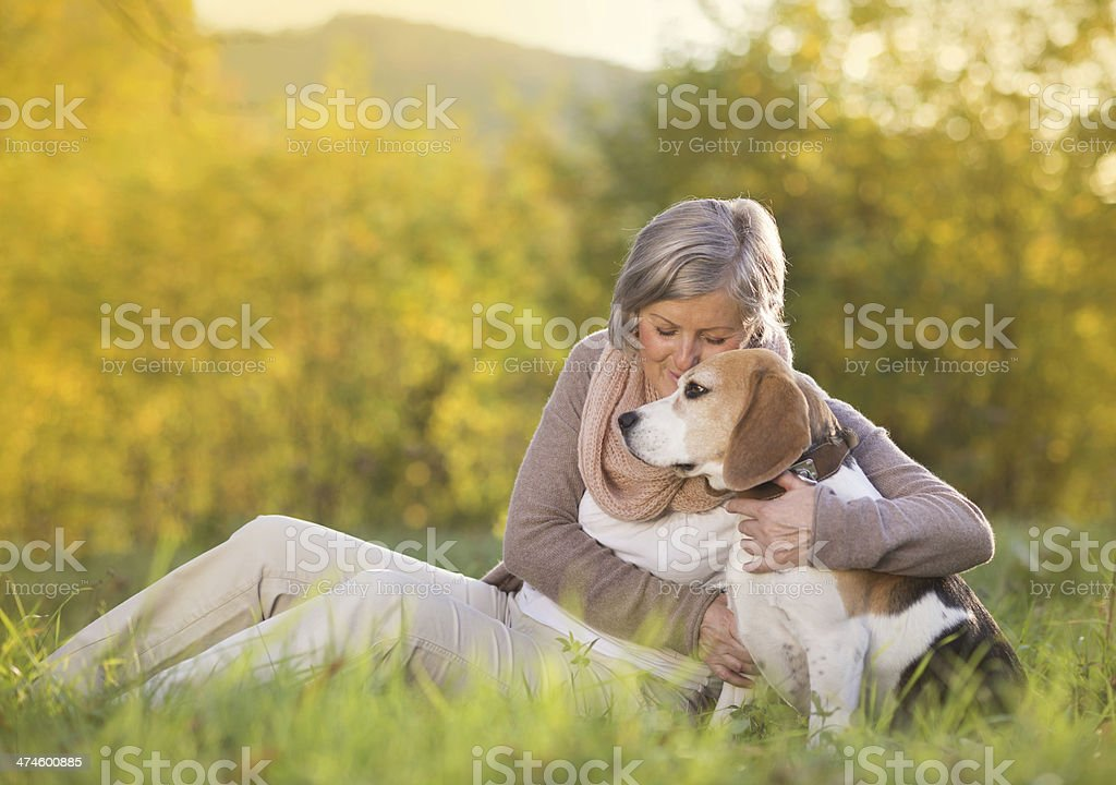 Active senior woman hugs dog stock photo