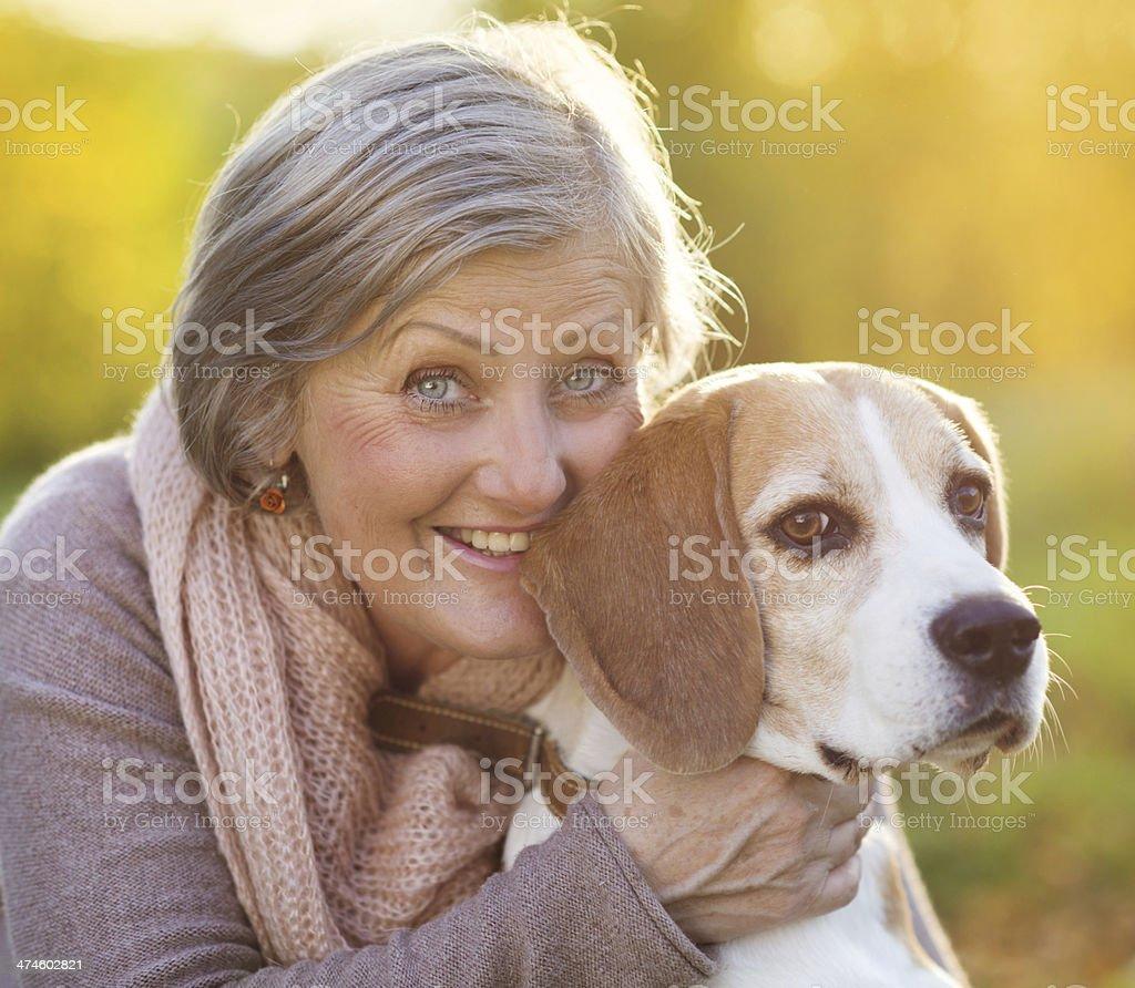 Active senior woman hugs dog royalty-free stock photo