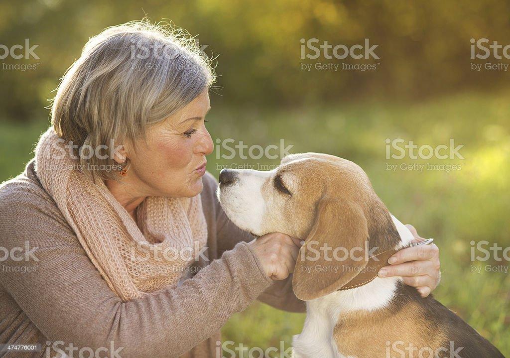 Active senior woman hugs dog stock photo