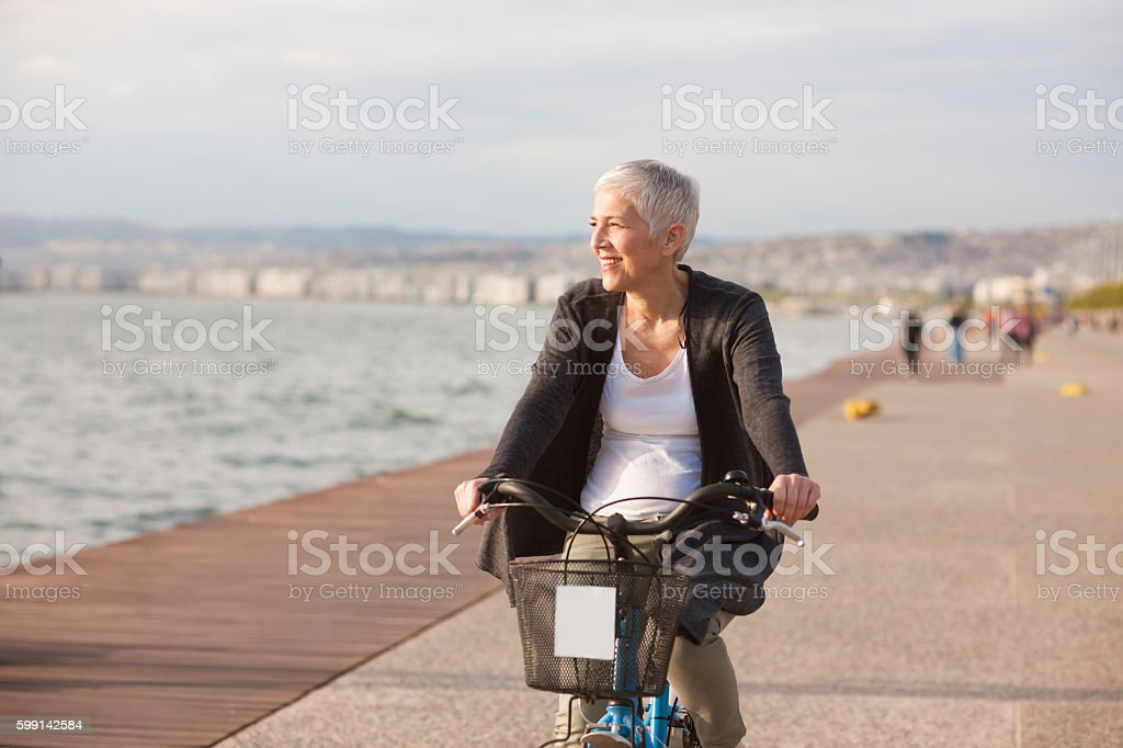 Active senior woman riding bicycle in the city stock photo