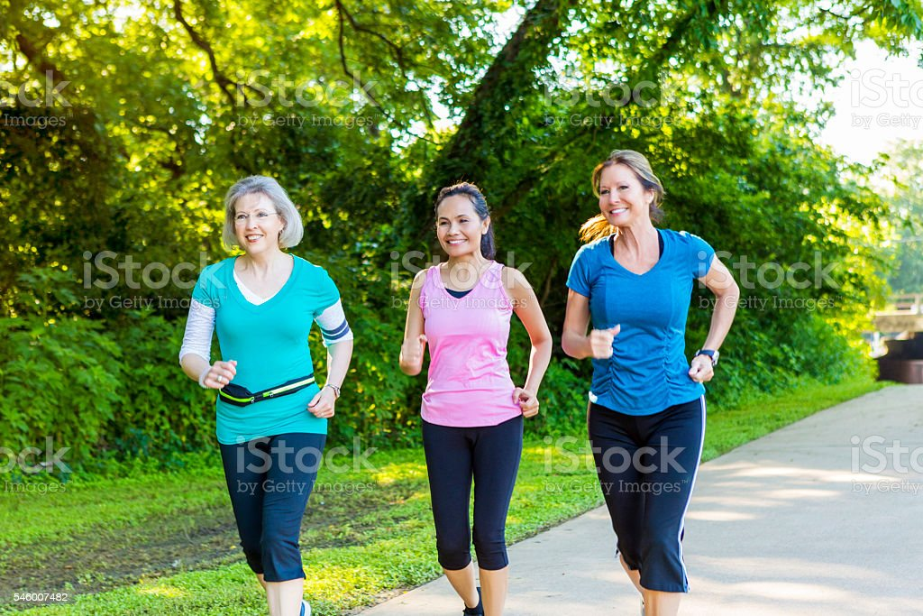 Active senior women jog together in park stock photo