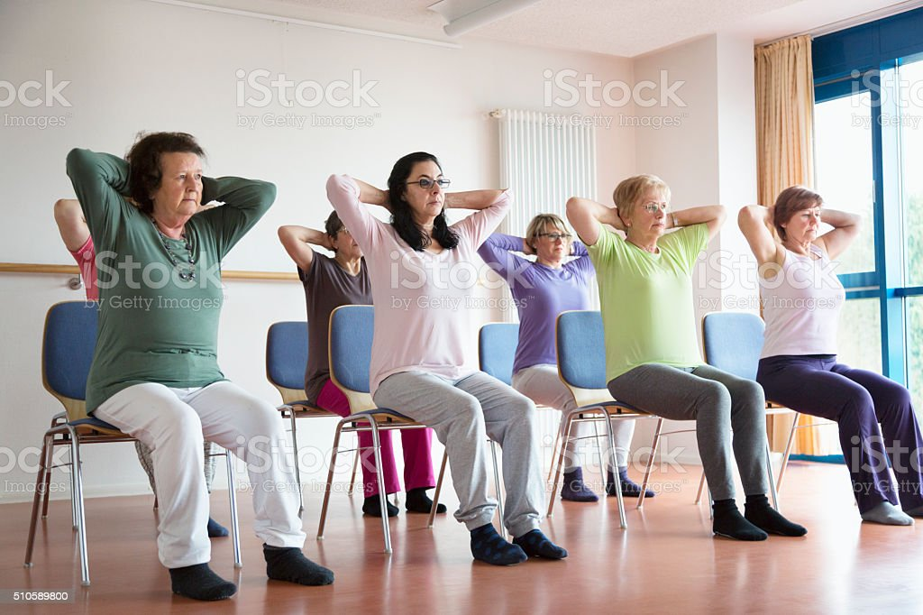 active senior women yoga class on chairs stock photo