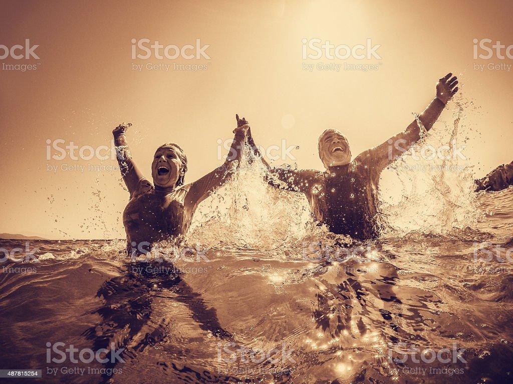 Active seniors bathing in the sea stock photo