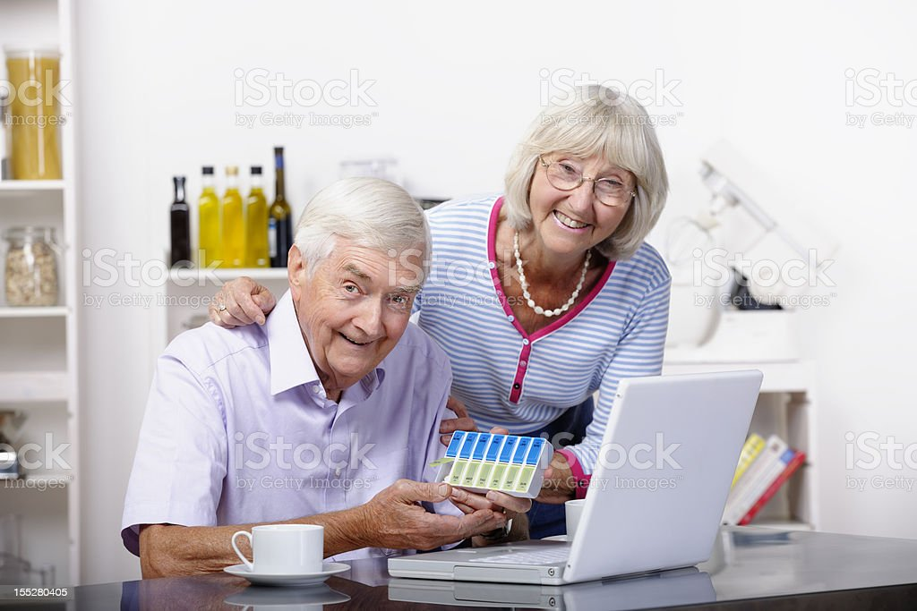 Active Seniors Dispensing Medication After Checking Details Online stock photo