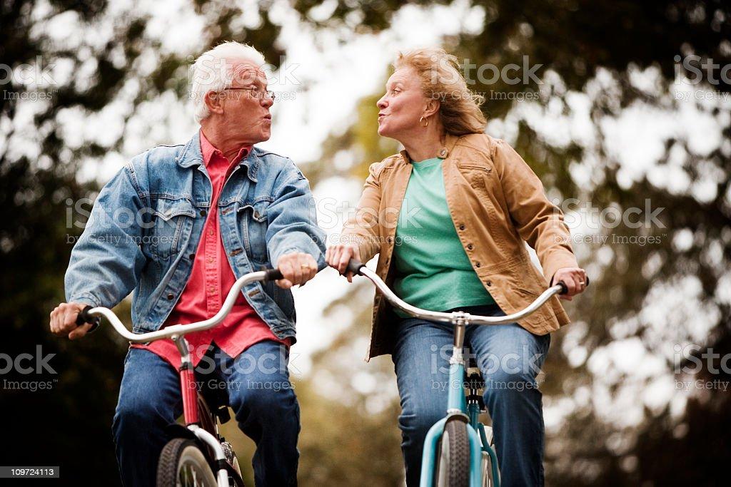 Active Seniors on Bike Throwing Kisses stock photo