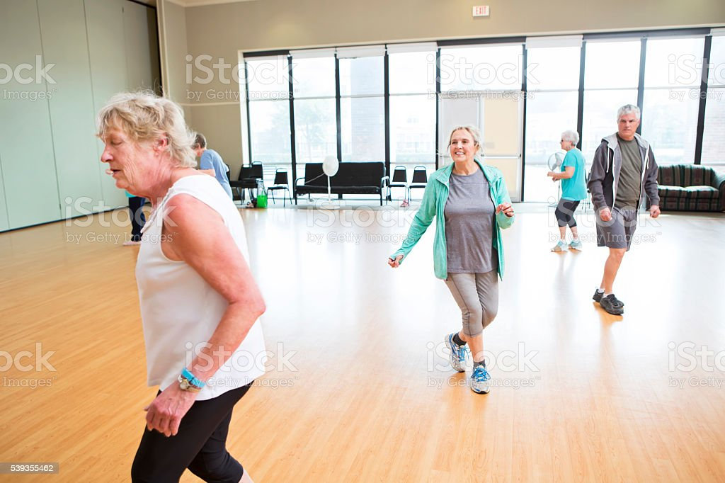 Active seniors particpate in dancing class stock photo