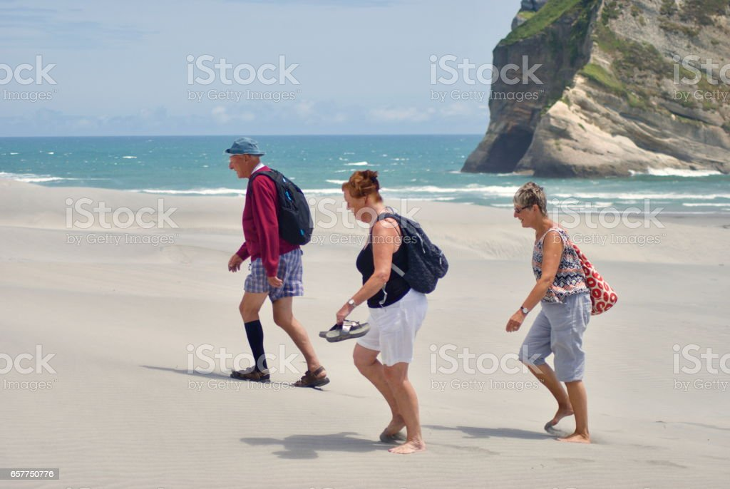 Active Seniors walking on the Beach stock photo