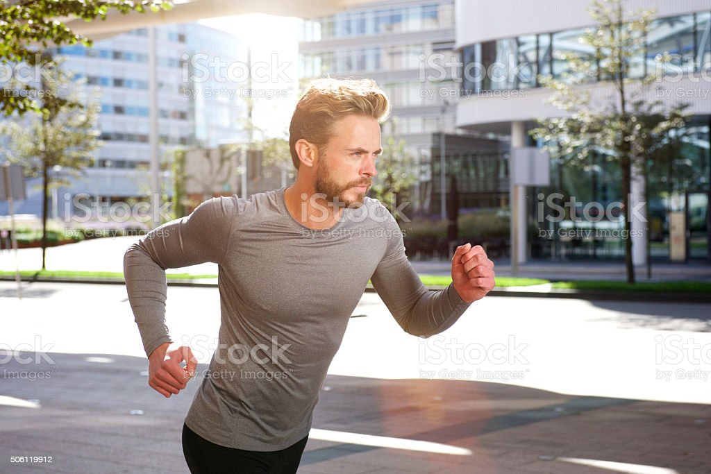 Active sports man running outside in the city stock photo