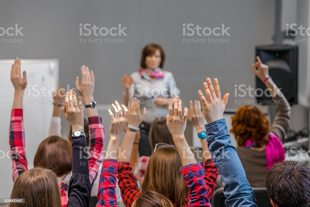 Active Students raising Arms up ready to answer Teachers Question stock photo