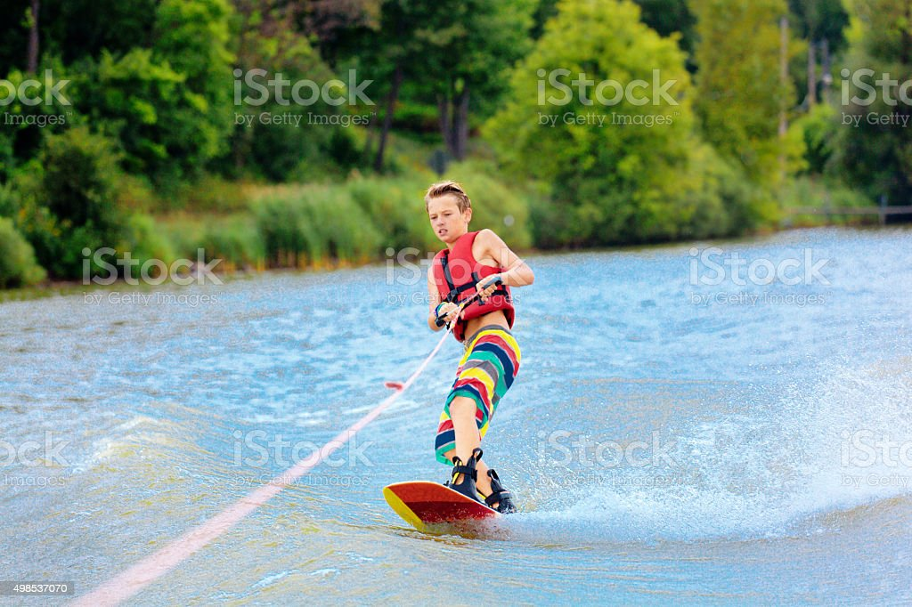 Active Teen Boy Water Ski Boarding on Lake in Summer stock photo