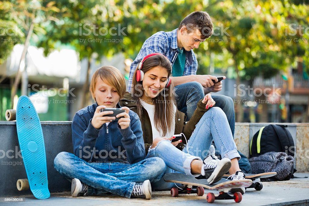 Active teens playing on smarthphones and listening to music stock photo
