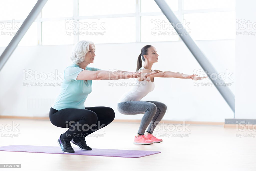 Active well built women squatting stock photo
