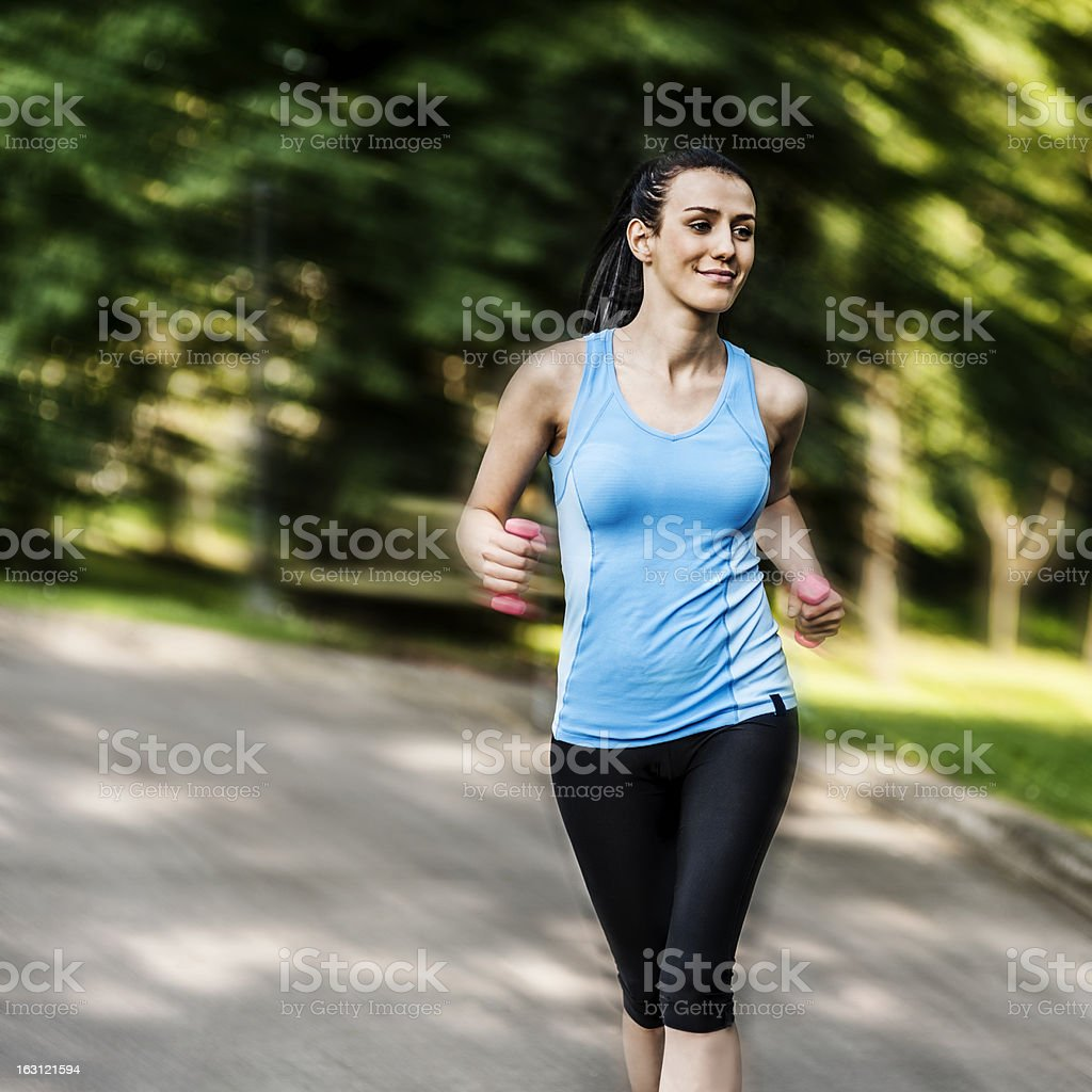 Active woman jogging with dumbbells royalty-free stock photo