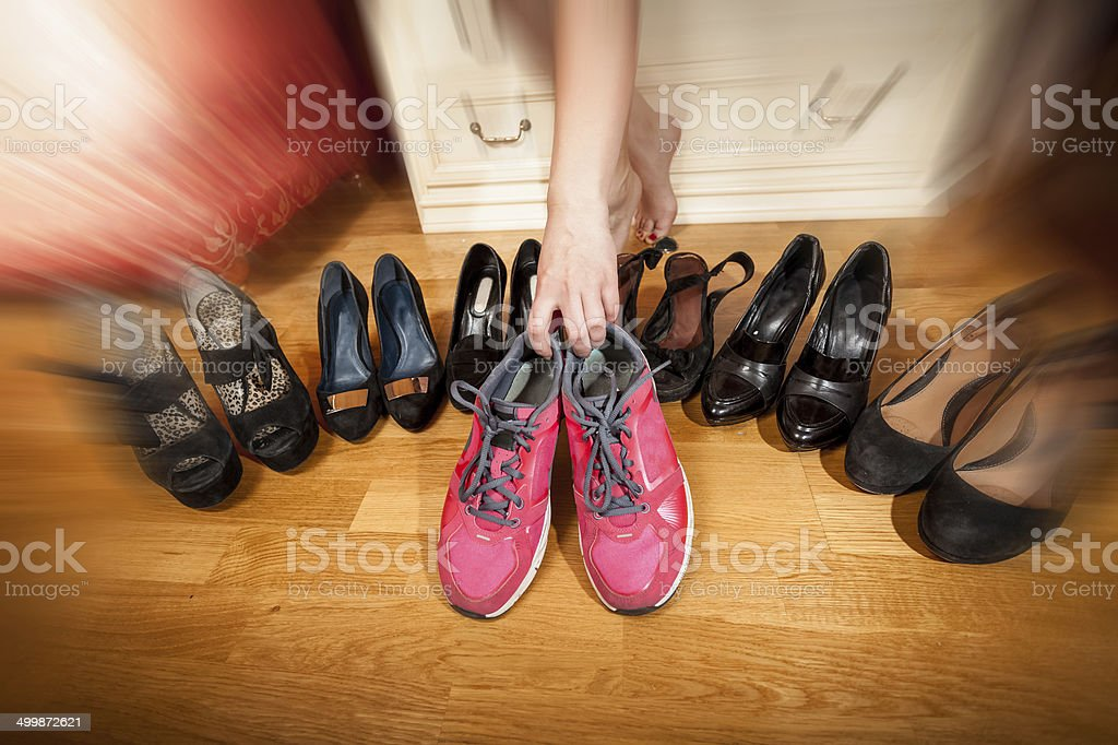active woman picking sneakers rather than high heels. Photo with royalty-free stock photo