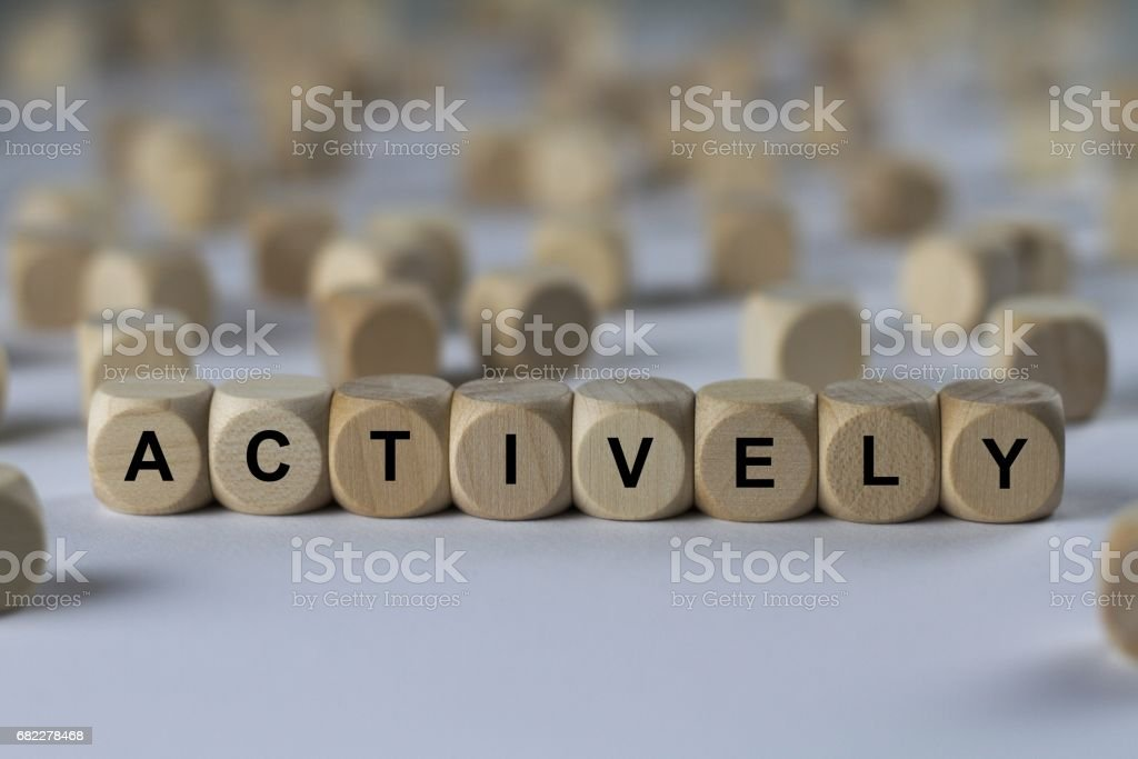 actively - cube with letters, sign with wooden cubes stock photo