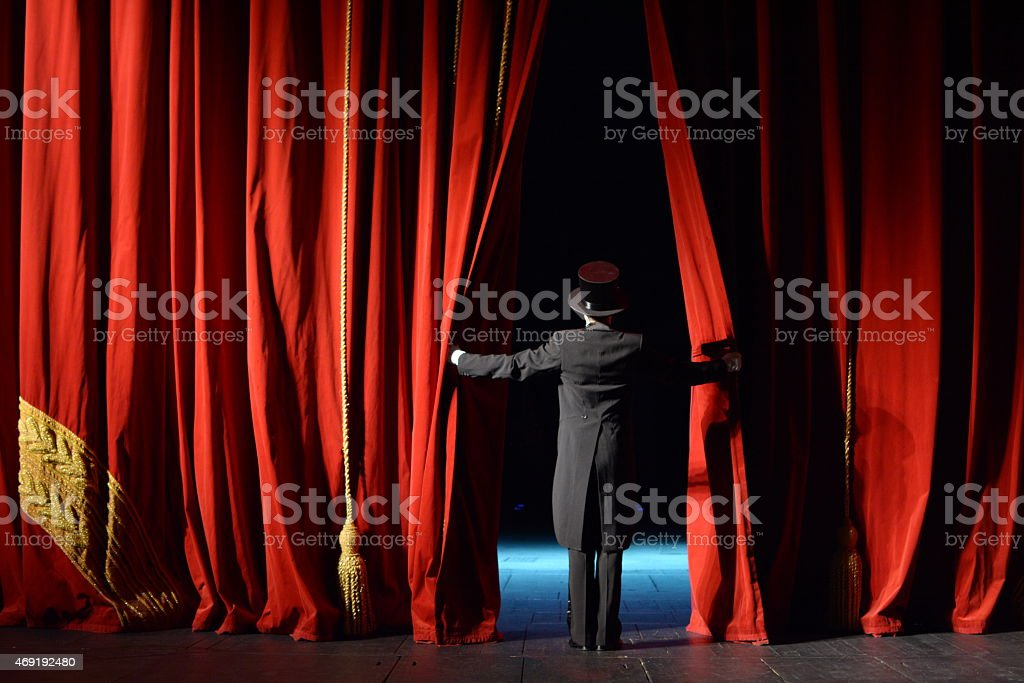 actor in a tuxedo stage curtain opens stock photo