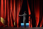 actor in a tuxedo stage curtain opens