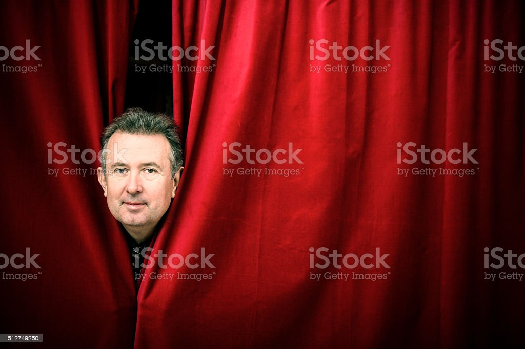 Actor peeking through curtain in the stage stock photo