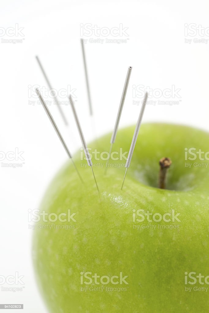 Acupuncture needles in Apple royalty-free stock photo