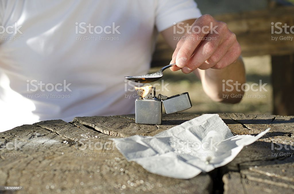 Addict heating cocaine in a spoon royalty-free stock photo