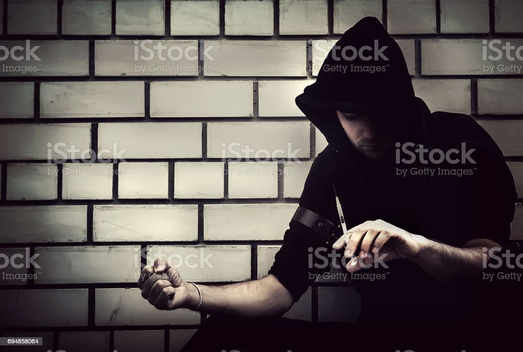 Addict with syringe wants to do an injection stock photo
