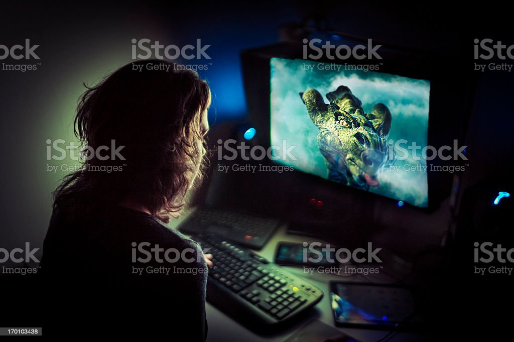 Addicted computer gamer playing late at night stock photo