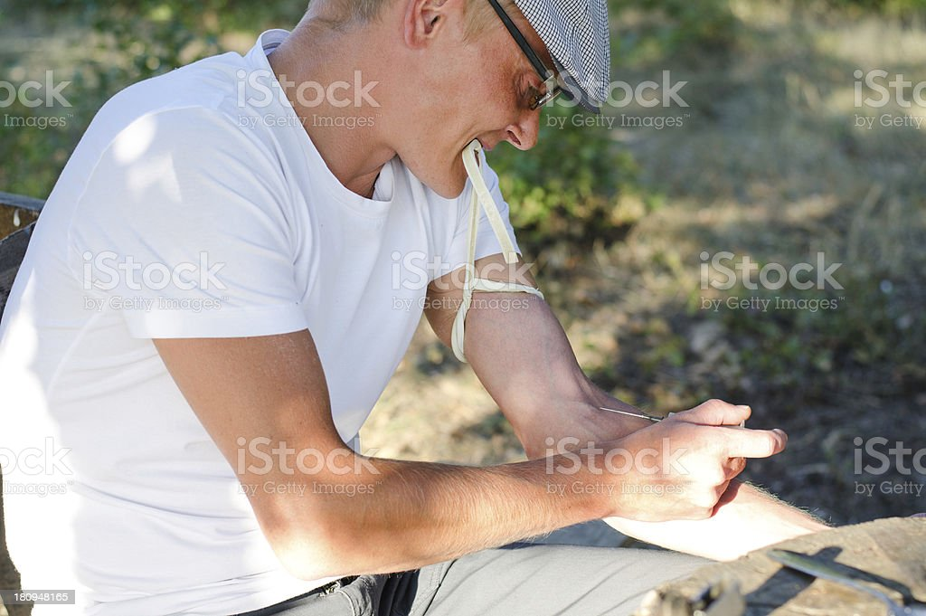 Addicted man injecting his tied arm intravenously royalty-free stock photo