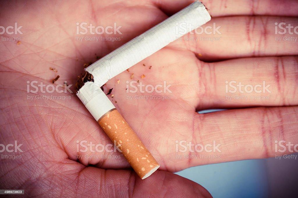 Addiction. Broken cigarette on hand. Quit smoking royalty-free stock photo