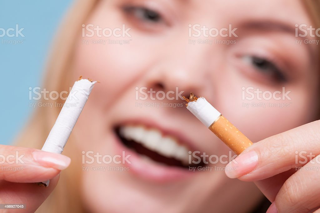Addiction. Girl breaking cigarette. Quit smoking. royalty-free stock photo
