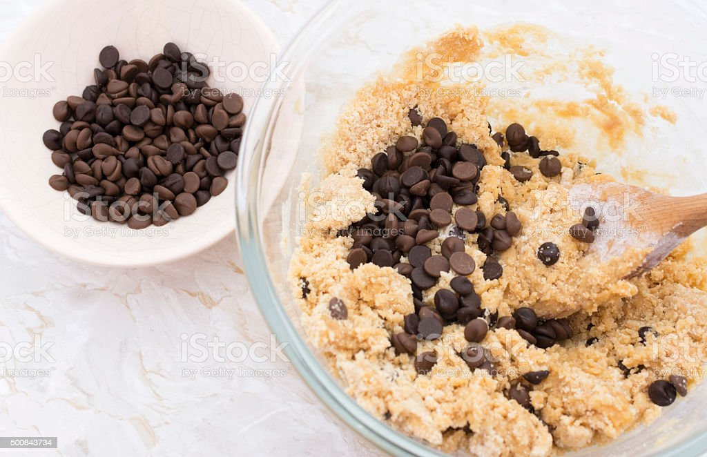 Adding chocolate chips to cookie dough stock photo