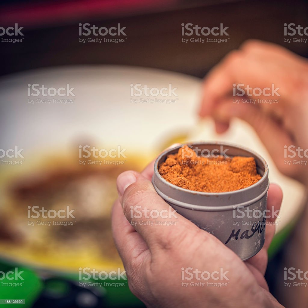 Adding Garam Masala Spice in a Dish stock photo