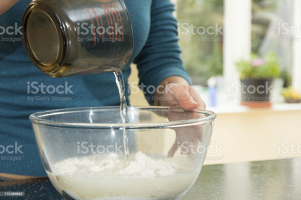 Adding water to a mixing bowl stock photo